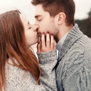 Young couple outdoor portrait. pretty girl kissing handsome boy