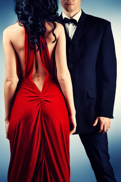 Beautiful young couple in love in evening dresses posing at stud